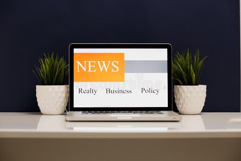 Укомплектуйте личным составом руки держа компьютер с экраном мировых новостей app в кафе стоковая фотография rf