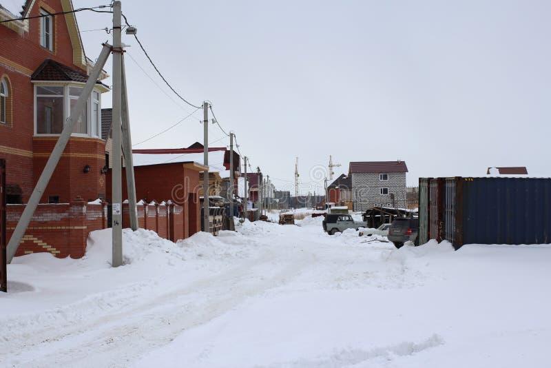 Улица снега в частном секторе Новосибирске около коттеджей в перемещении зимы к строительной площадке стоковое фото rf
