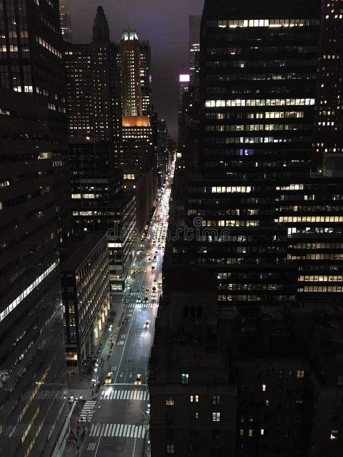 Улицы Нью-Йорка с потоком автомобилей и высоких освещенных небоскребов против ночного неба стоковые фотографии rf