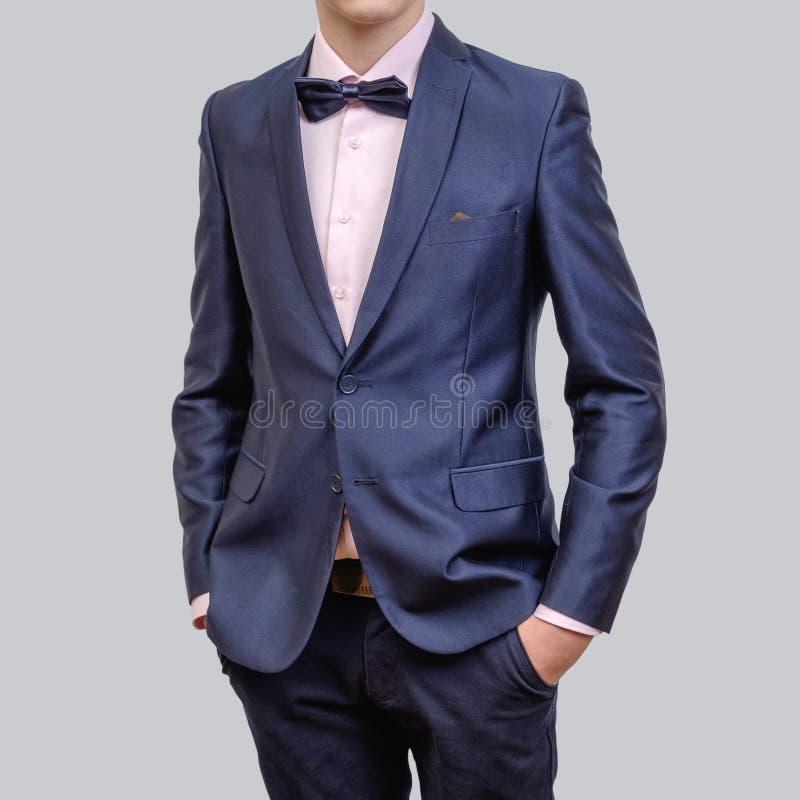 Ультрамодный молодой человек нося смычок голубого блейзера и связи, стоя против серой предпосылки стоковые изображения
