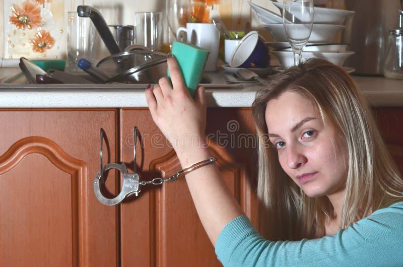 Унылая и утомленная девушка надеванная наручники к счетчику кухни с много стоковые фото
