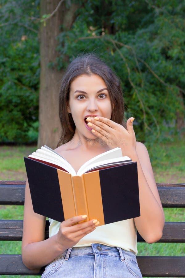 Удивленная милая девушка читает книгу и покрывает ее рот с рукой снаружи стоковая фотография rf
