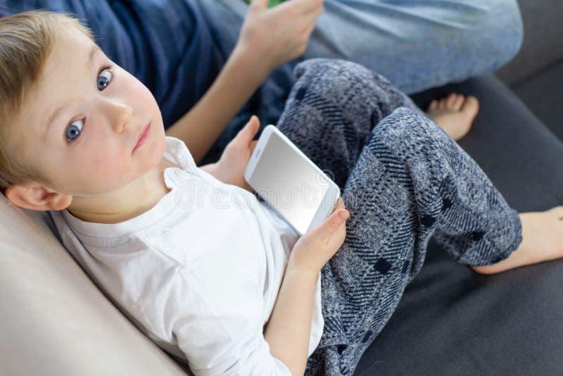 Усаживание мальчика, смотря камеру и используя мобильный умный телефон дома Руки hild ¡ Ð со смартфоном стоковая фотография rf