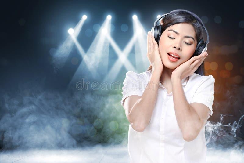 Усмехаясь азиатская женщина в музыке белой рубашки слушая с наушниками стоковые фотографии rf