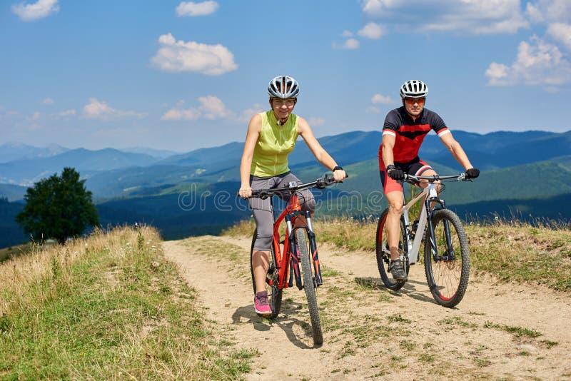 Усмехаясь велосипедисты соединяют человека и женщины в sportswear и шлемов задействуя велосипеды по пересеченной местностей стоковое фото rf