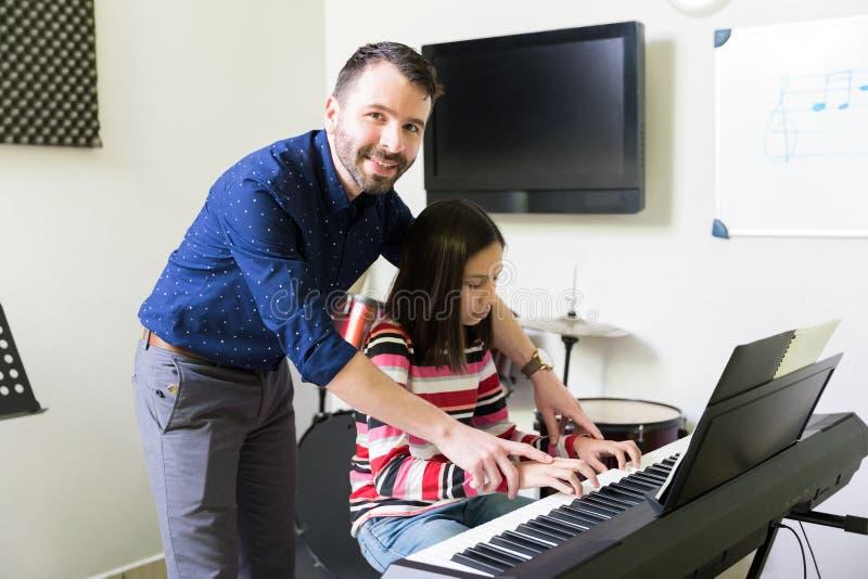 Усмехаясь гувернер помогая девушке в игре электрического рояля стоковые фото