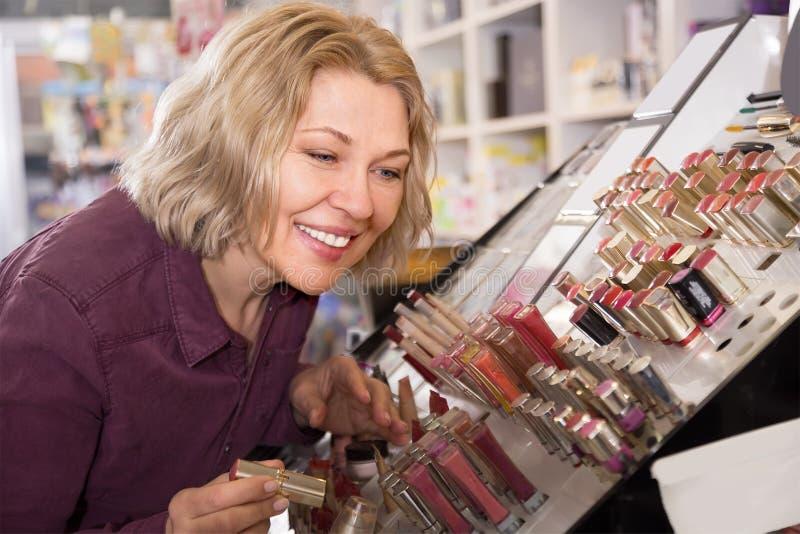 Усмехаясь женский клиент покупая красную губную помаду стоковое фото rf