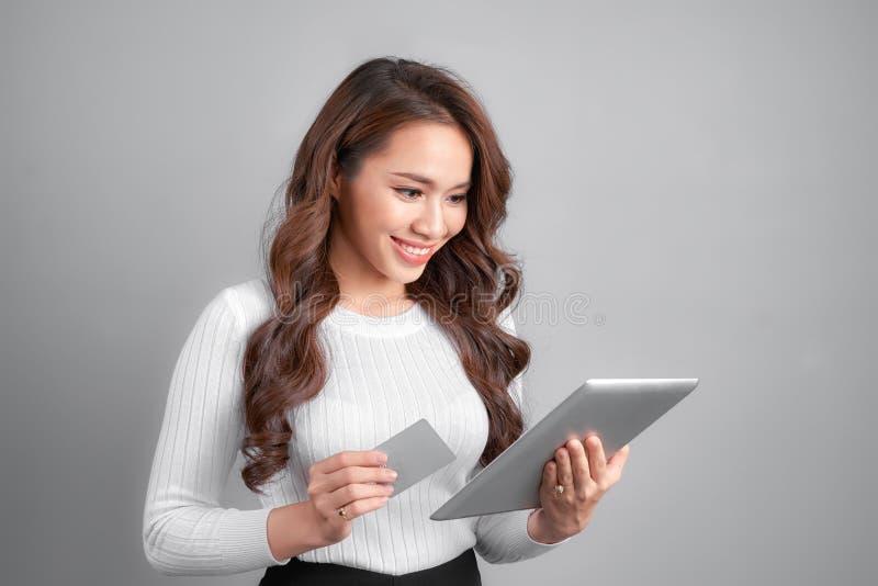 Усмехаясь женщина показывая кредитную карточку кредита без обеспечения держит ПК таблетки в руке, изолированной над белой предпос стоковое фото rf