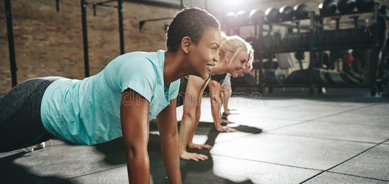 Усмехаясь женщина делая pushups с друзьями во время разминки спортзала стоковые изображения rf