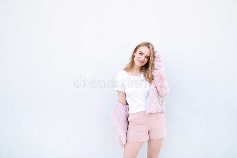 Усмехаясь красивый девочка-подросток в розовых шортах и положении пальто на белой предпосылке стоковая фотография