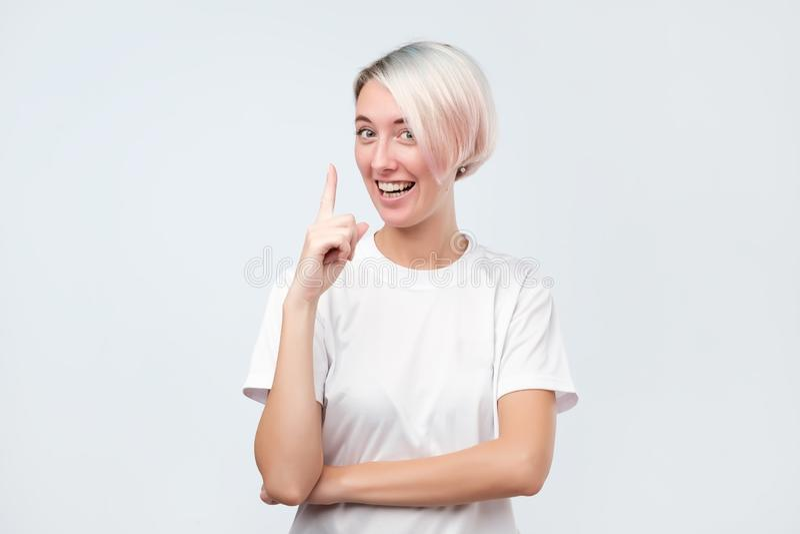 Усмехаясь милая девушка указывая указательный палец вверх по давать совет стоковые фотографии rf