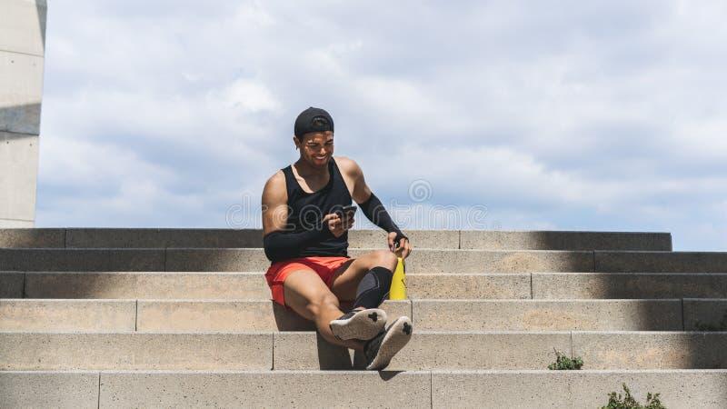 Усмехаясь мышечный подходящий спринтер человека спорта отдыхая после его разминки и использования мобильного телефона широко стоковое изображение rf