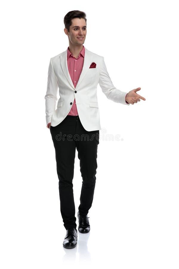 Усмехаясь молодой бизнесмен идя и показывать жестами стоковое фото
