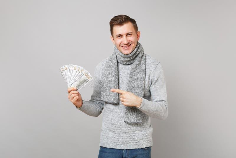 Усмехаясь молодой человек в сером свитере, шарфе указывая указательный палец на пуке серий денег наличных денег банкнот долларов  стоковые фото
