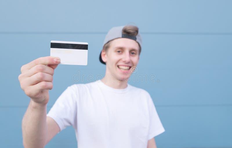 Усмехаясь молодой человек держит карту банка в его руках и улыбках на пастельной голубой предпосылке стоковое изображение