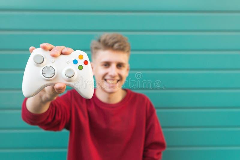 Усмехаясь молодой gamer с gamepad в его руке на фоне стены бирюзы стоковая фотография