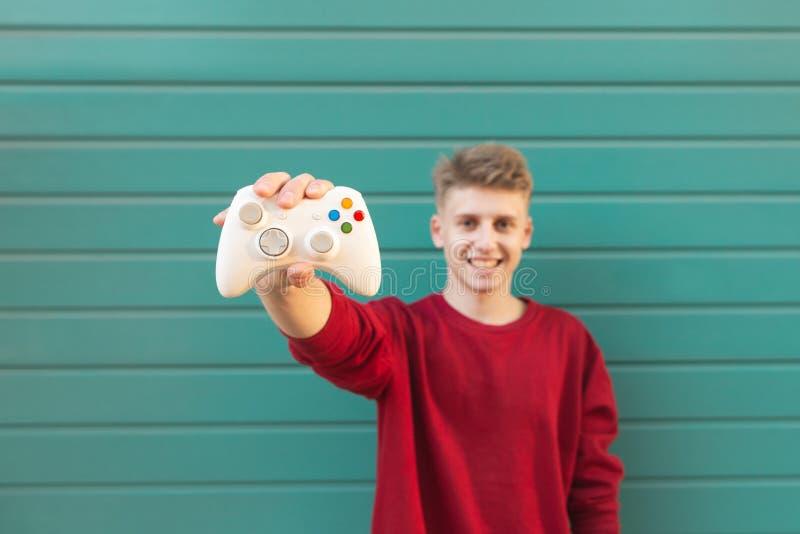Усмехаясь молодой gamer с gamepad в его руке на фоне стены бирюзы стоковое фото
