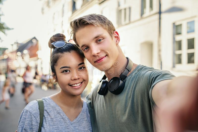 Усмехаясь пары принимая selfies совместно на улицу города стоковые изображения rf