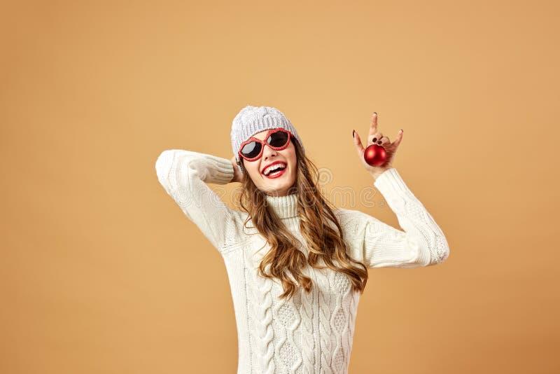 Усмехаясь девушка в солнечных очках одетых в белых связанных свитере и шляпе держит красный шарик рождества на бежевой предпосылк стоковые изображения