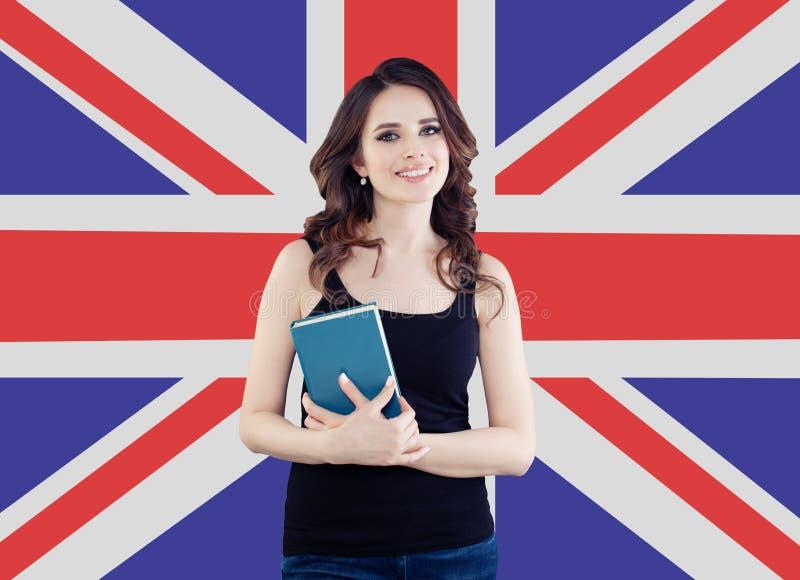 Усмехаясь девушка на предпосылке флага Великобритании Милая жизнерадостная женщина уча английский язык и путешествуя в Великобрит стоковое изображение rf