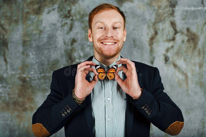 Усмехаясь человек в куртке и рубашке с бабочкой как бабочка Как связать концепцию бабочки стоковое фото rf