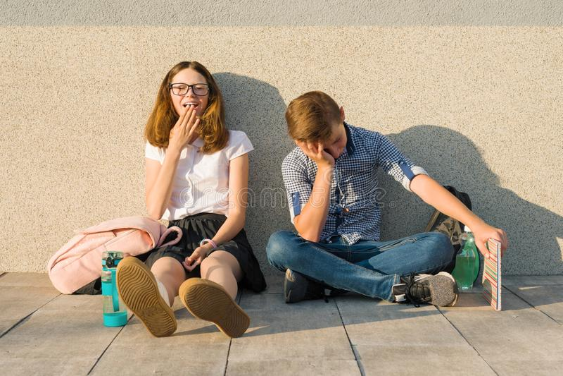 Уставшие подростки школьников сидя снаружи на серой стене с книгами, рюкзаками стоковые изображения rf