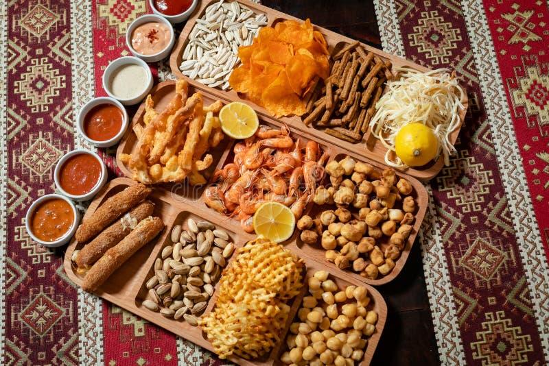Установите закусок пива, 11 разнообразий и 6 соусов на деревянном столе со скатертью с национальными картинами стоковая фотография