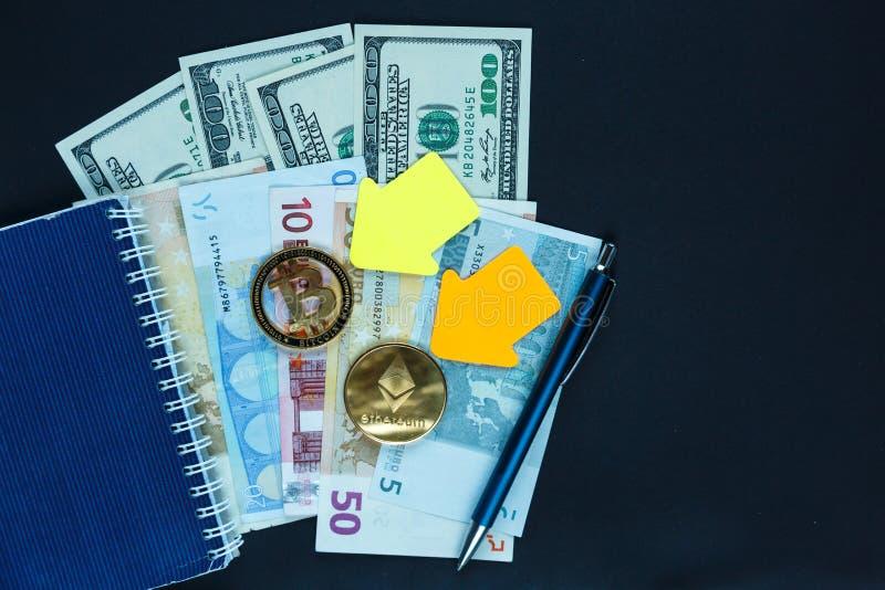 Установите bitcoin, ethereum - секретной валюты с желтыми бумажными стрелками рядом с блокнотом на реальной предпосылке денег стоковое фото rf