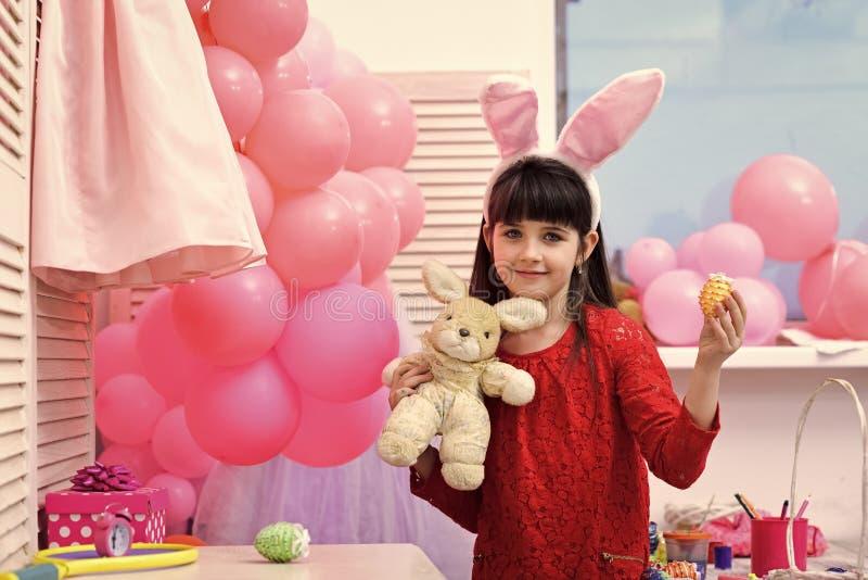 Уши зайчика прелестной маленькой девочки нося держа пасхальные яйца стоковое изображение
