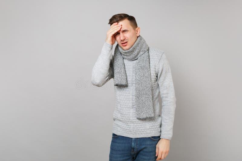 Утомлянный расстроенный молодой человек в сером свитере, шарфе имея головную боль, положил руку на голову на серой предпосылке ст стоковые фотографии rf