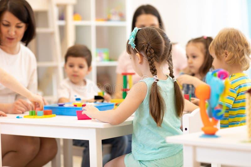 Учитель и ассистентская игра с детьми в детском саде стоковые фотографии rf
