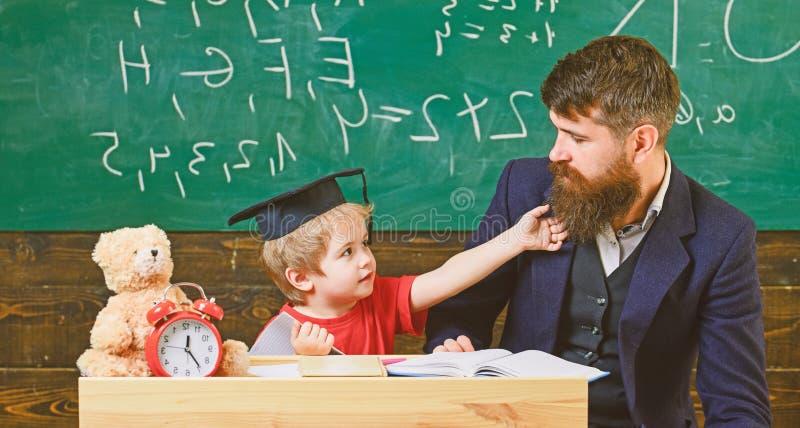 Учитель и зрачок в mortarboard, доске на предпосылке Отвлекать ребенк жизнерадостный пока изучающ, синдром дефицита внимания стоковое фото rf