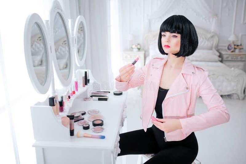 Урод моды Девушка очарования синтетическая, поддельная кукла с пустым взглядом и короткие черные волосы держат губную помаду пока стоковые фотографии rf