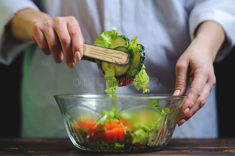 Шеф-повар подготавливает вегетарианский салат овоща стоковая фотография