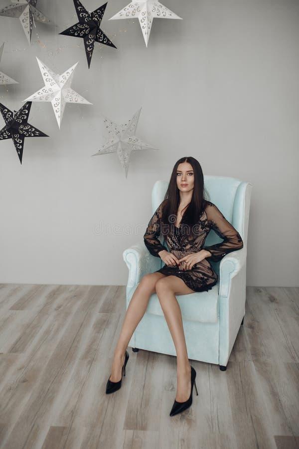 Шикарная модель брюнета в черных платье и пятках в кресле стоковая фотография rf