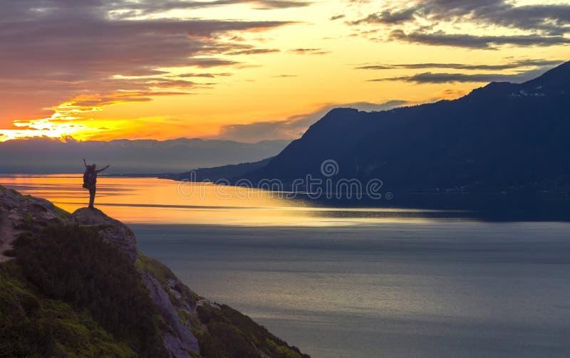 Широкая панорама озера горы Небольшой силуэт туриста с рюкзаком на наклоне скалистой горы с поднятыми руками на воде озера стоковые фотографии rf