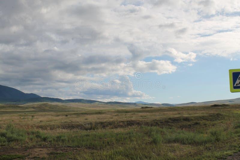 Широкая степь с желтой травой под голубым небом с белизной заволакивает горы Sayan Сибирь Россия стоковые фото
