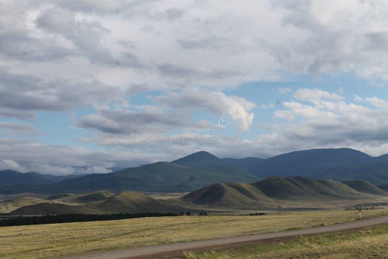 Широкая степь с желтой травой под голубым небом с белизной заволакивает горы Sayan Сибирь Россия стоковые изображения