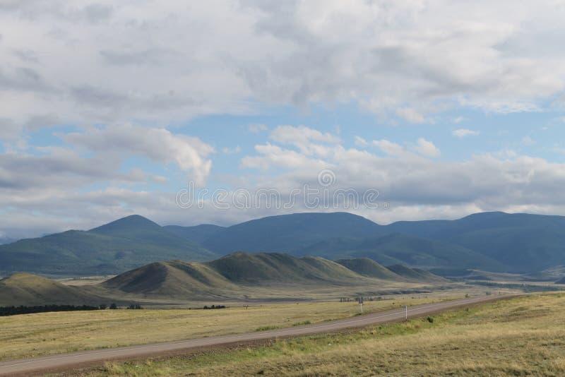 Широкая степь с желтой травой под голубым небом с белизной заволакивает горы Sayan Сибирь Россия стоковое изображение rf