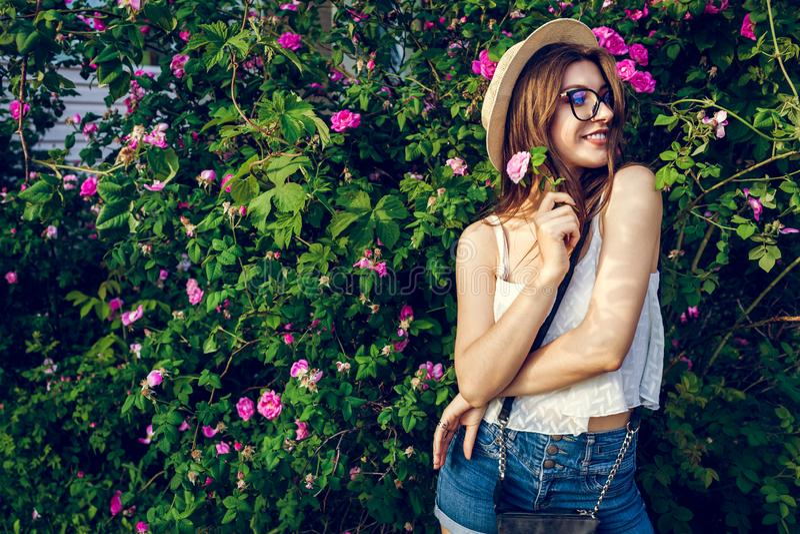 Шляпа молодой девушки битника нося идя путем зацветая розы Женщина наслаждается цветками в парке Обмундирование лета стоковые изображения rf