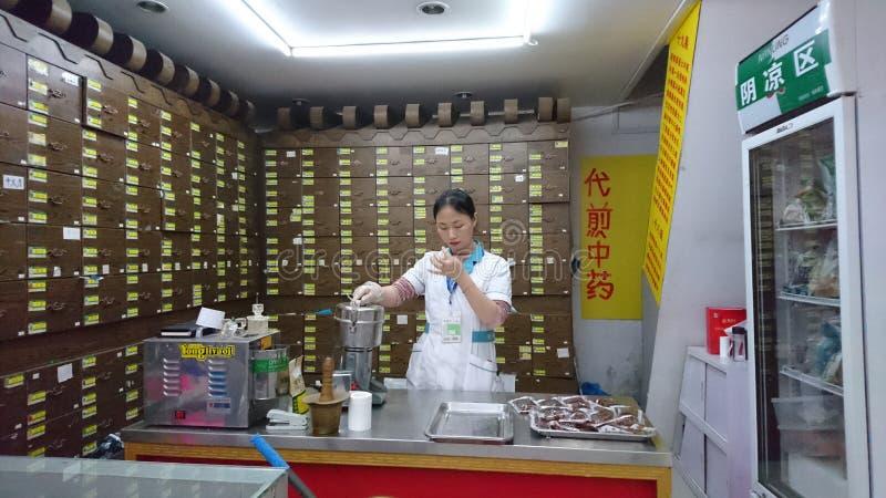 Шэньчжэнь, Китай: Женские аптекари отжимая медицины машиной стоковое изображение
