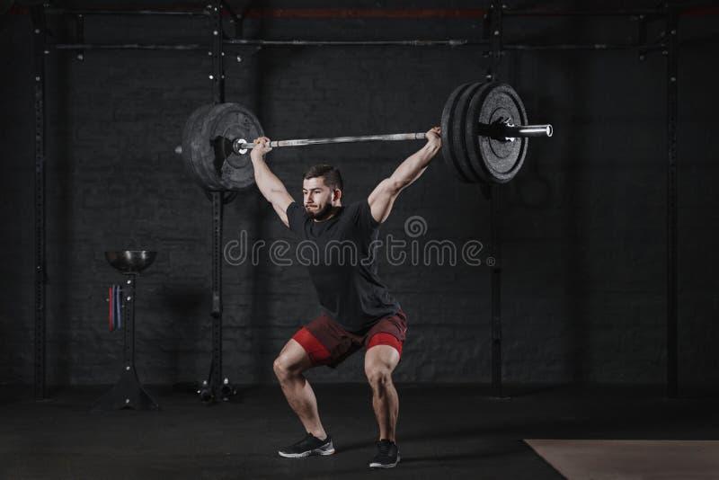 Штанга молодого спортсмена crossfit поднимаясь наверху на спортзале Человек практикуя функциональные тренируя powerlifting тренир стоковое изображение