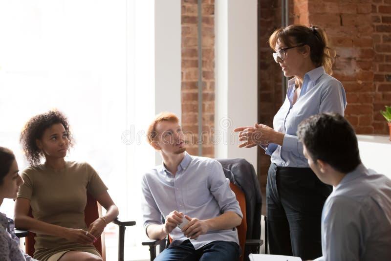 Штат серьезного руководителя тренера говоря уча разнообразный на групповой встрече стоковое фото