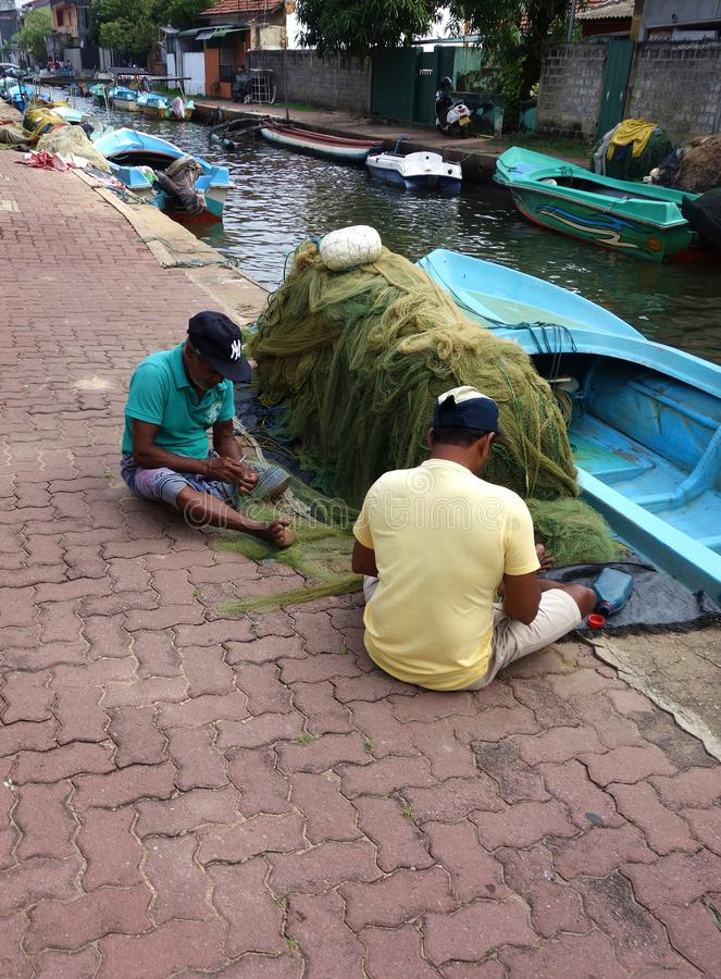 Шриланкийск рыболов шить их рыболовные сети стоковое фото rf