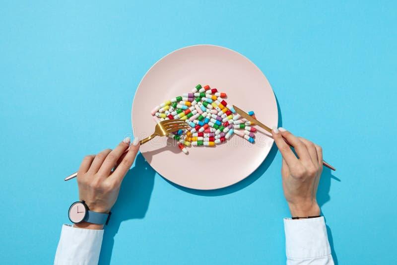 Таблетки и планшеты витамина в форме o рыба в руке плиты и женщины с дозором на голубой предпосылке Плоское положение стоковые изображения rf