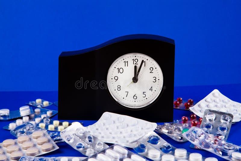 Таблетки и часы стоковые фото