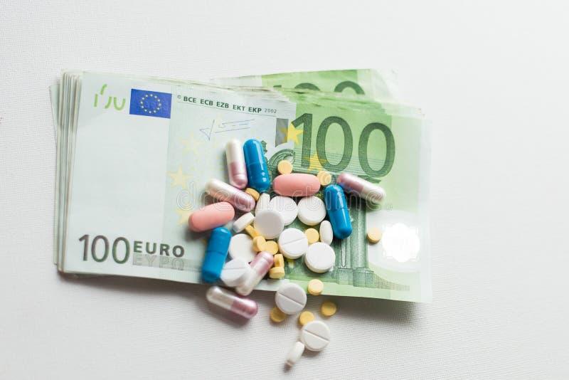 Таблетки на деньгах евро изолированных на белой предпосылке Расходы медицины установьте текст стоковое фото rf