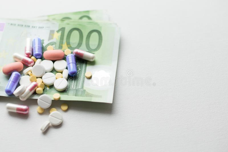 Таблетки на деньгах евро изолированных на белой предпосылке Расходы медицины установьте текст стоковое изображение rf