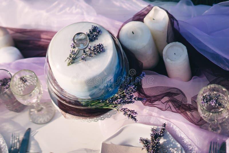 Таблица свадьбы с тортом, лавандой и свечами стоковая фотография rf