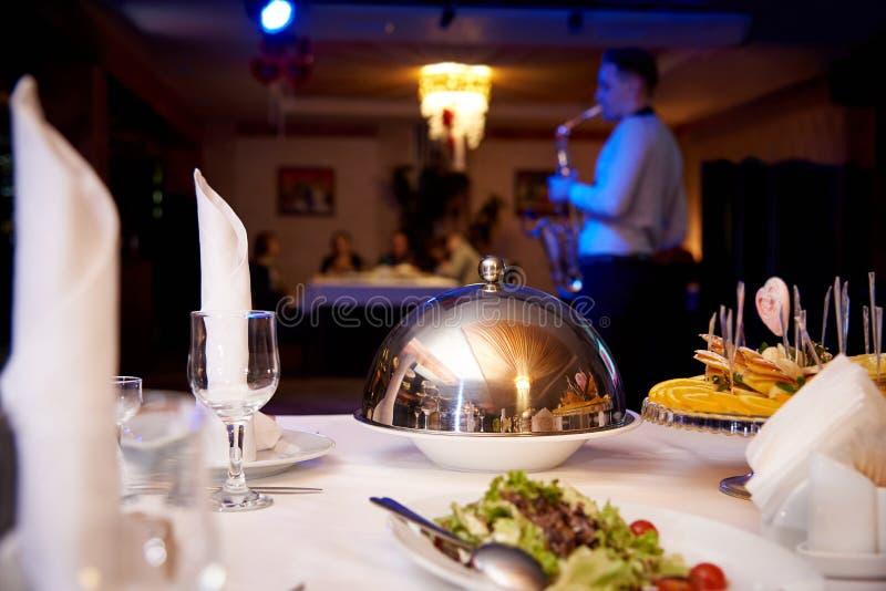 таблица служят обедом, котор Горячее блюдо на подносе купола на таблице сервера на запачканной предпосылке играя саксофониста для стоковая фотография